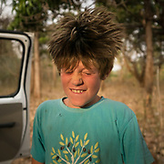 Boy shakes his head fast. Hair flying in the air.
