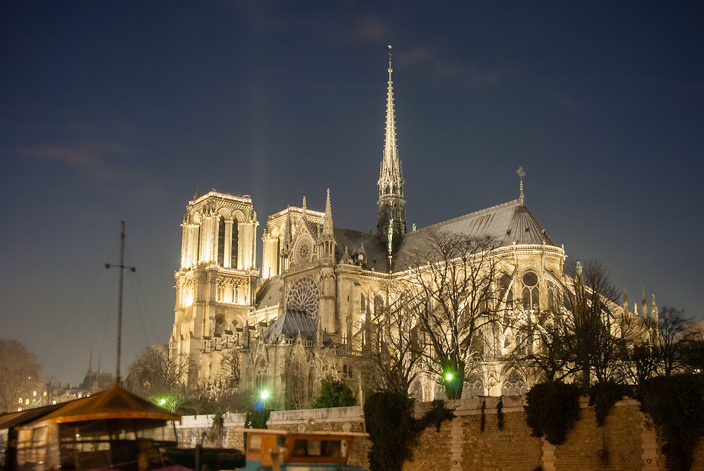 Rear view of Notre Dame Cathedral, Paris, at night with riverboats.