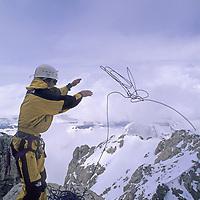 MOUNTAINEERING. Grand Teton National Park, Wyoming. Kristoffer Erickson (MR) throws rappel rope down Owen-Spaulding route of Grand Teton.