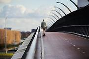 Elderly man walks on empty bike path | Oudere man loopt over leeg fietspad