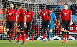 Manchester United players stand dejected after conceding the first goal during the UEFA Champions League round of 16, first leg match at Old Trafford, Manchester.