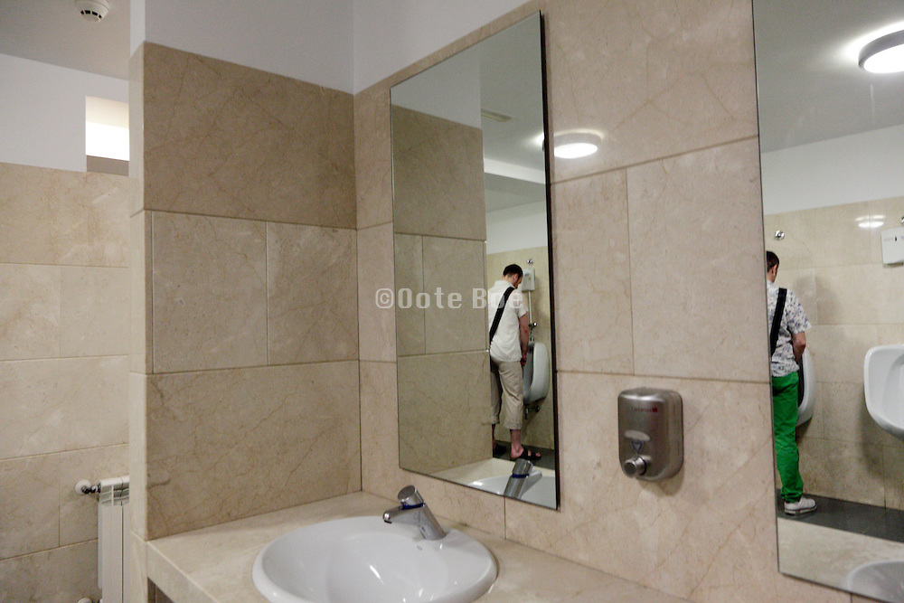 male public toilet with two people in the mirror