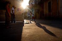 cuban friends playing stickball in street