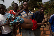 Men carry a boy, who died shortly after from a gunshot wound during a violent confrontation between Muslims and Christians, in Miskine district in the capital Bangui January 24, 2014.