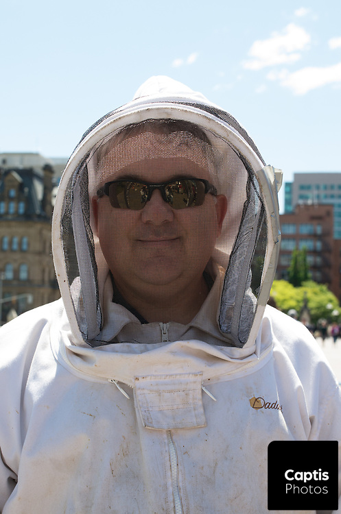 """A bee keepers, who later spoke to the demonstration about the """"100% loss"""" of his bee population poses for a photo. May 31, 2014."""