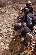 Pioneers in blue flak jackets and helmets probing for landmines uncover a small hockey puck size landmine near a new training camp for 229 volunteers in Hargeisa, Somaliland. Somaliland is the breakaway republic in northern Somalia that declared independence in 1991 after 50,000 died in civil war. March 1992.