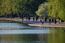 Commuters, walkers and runners walk along the edge of the boating lake as a beautiful morning greets Londoners in Regents Park. London, May 09 2018.
