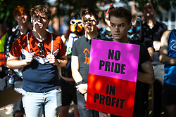 """© Licensed to London News Pictures . 28/08/2021. Manchester, UK. A """"bno pride in profit """" banner in carried at the demo . People take part in a Reclaim Pride march through Manchester City Centre , in opposition to the management of the city's """"official"""" Manchester Pride charity festival . The Manchester Pride charity parade was cancelled in 2020 due to Coronavirus . An """"equality march"""" organised by Manchester Pride charity was due to take place on Deansgate as the protest passed through the Gay Village . Protesters object to Manchester Pride charity's withdrawal of funding for the LGBT Foundation's condom distribution scheme and HIV charity George House Trust as well as increasing commercialisation of the annual event . Photo credit: Joel Goodman/LNP"""