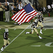 UCF football players enter the field carrying an American flag in remembrance of 9/11, during an NCAA football game between the Boston College Eagles and the UCF Knights at Bright House Networks Stadium on Saturday, September 10, 2011 in Orlando, Florida. (AP Photo/Alex Menendez)