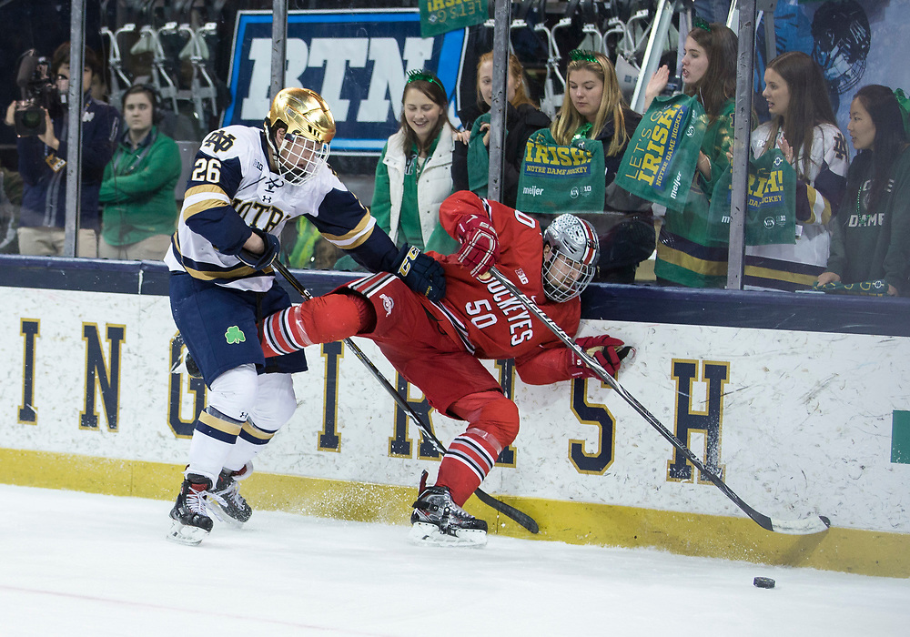 March 17, 2018:  Notre Dame forward Cam Morrison (26) and Ohio State defenseman Matt Miller (50) battle along the boards during NCAA Hockey game action between the Notre Dame Fighting Irish and the Ohio State Buckeyes at Compton Family Ice Arena in South Bend, Indiana.  Notre Dame defeated Ohio State 3-2 in overtime.  John Mersits/CSM