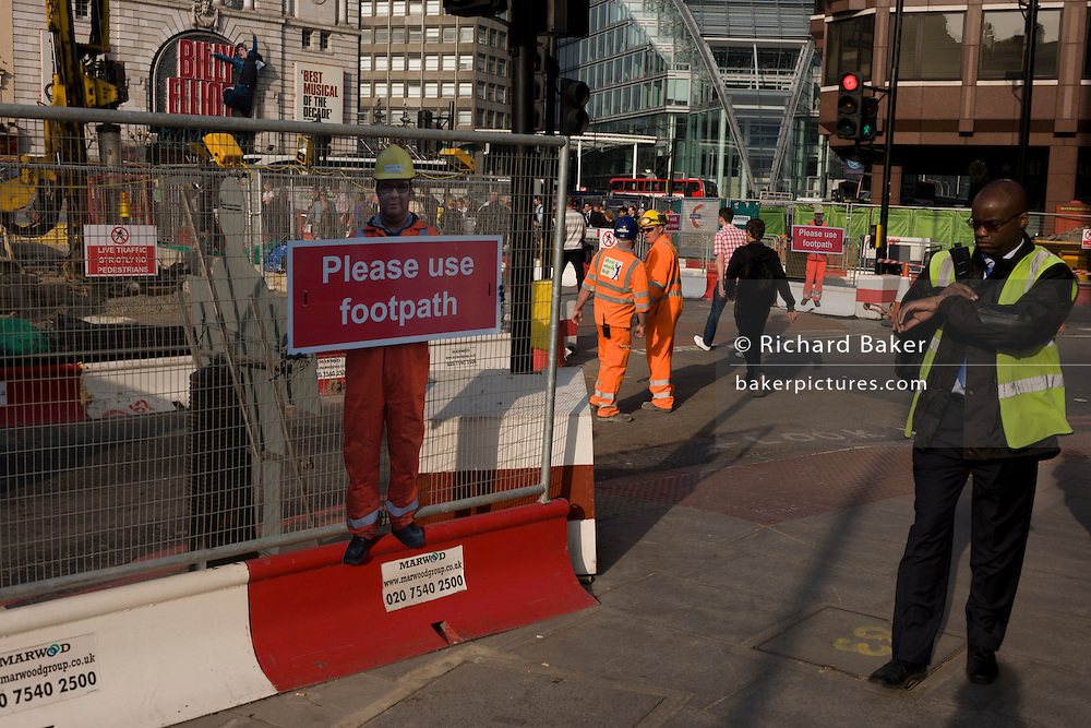 Man checks his watch near a scaled human workman figure who warns pedestrians to stay on established footpath, and not wander into construction site roadways.