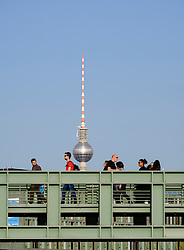 Pedestrians walk over footbridge crossing River Spree with Fernsehturm , television tower, to rear in Berlin Germany