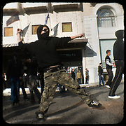 Rioting in front of King George street in Syntagma Athens. <br /> <br /> Following the murder of a 15 year old boy, Alexandros Grigoropoulos, by a policeman on 6 December 2008 widespread riots, protests and unrest followed lasting for several weeks and spreading beyond the capital and even overseas<br /> <br /> When I walked in the streets of my town the day after the riots I instantly forgot the image I had about Athens, that of a bustling, peaceful, energetic metropolis and in my mind came the old photographs from WWII, the civil war and the students uprising against the dictatorship. <br /> <br /> Thus I decided not to turn my digital camera straight to the destroyed buildings but to photograph through an old camera that worked as a filter, a barrier between me and the city.
