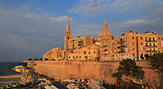 Golden warm evening light on buildings and churches Valletta, Malta, dome Basilica of Our Lady of Mount Carmel church