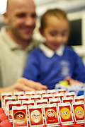 A father playing 'Guess Who' with his daughter in the visitors centre with Inside innovations, homework club, HMP Wandsworth.