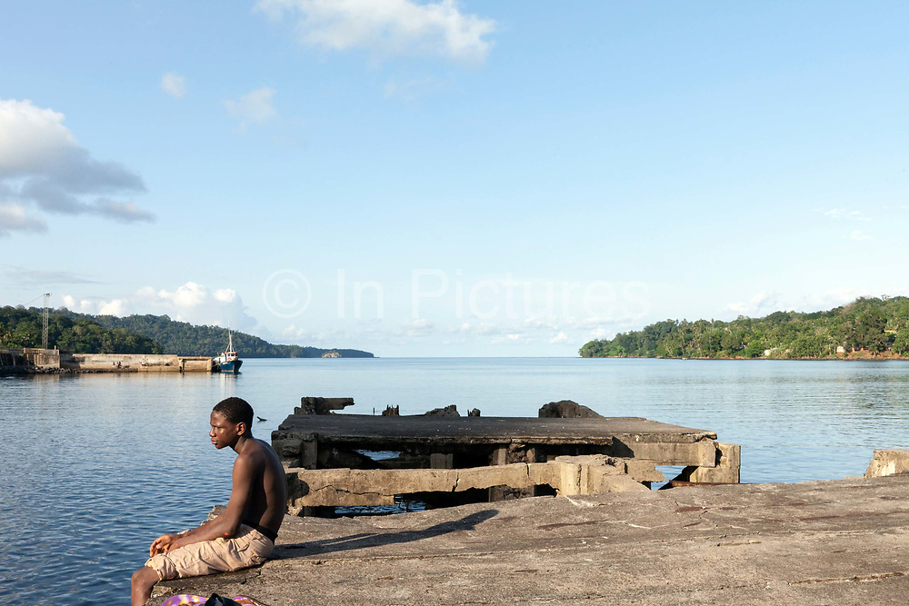 A boy sits on the pier of the harbour of the capital, Santo António, Principe. Sao Tome and Principe, are two islands of volcanic origin lying off the coast of Africa. Settled by Portuguese convicts in the late 1400s and a centre for slaving, their independence movement culminated in a peaceful transition to self government from Portugal in 1975.