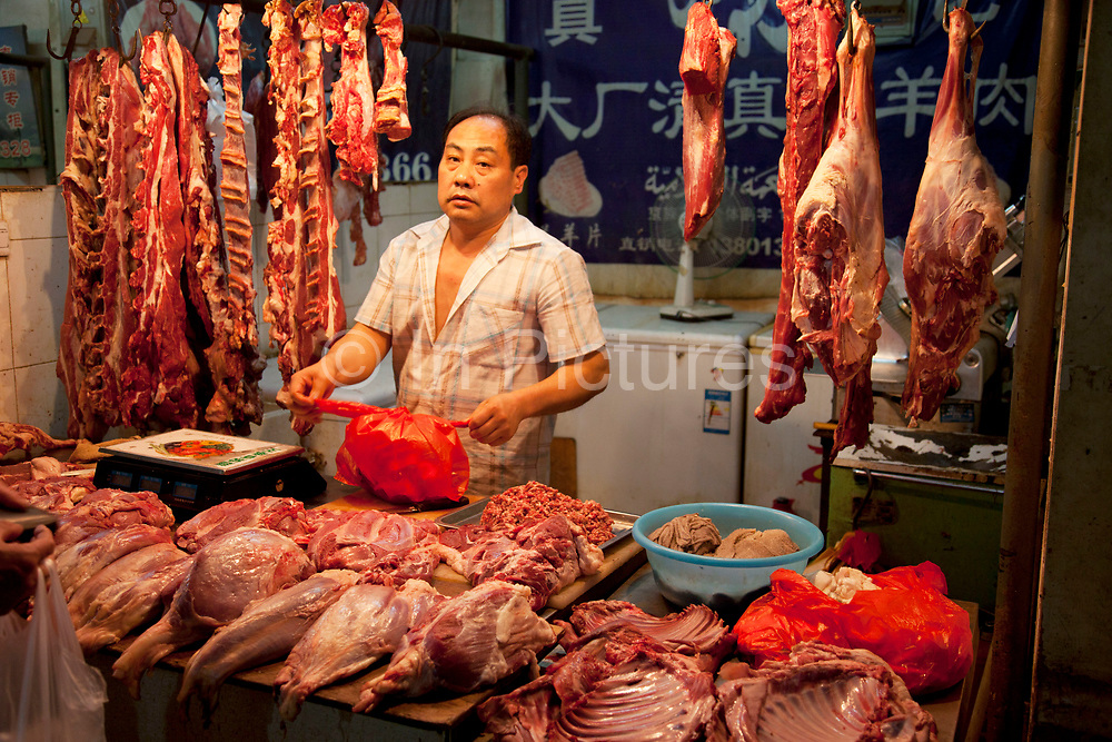 Meat seller on a stall at in indoor wet market in an old Chinese style area of Fuchengmen, in the Xicheng district of Beijing, China. This neighbourhood, tucked away behind a major road had people selling food in the street as well as in this covered market.