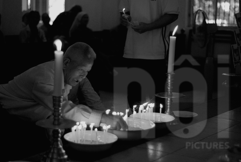 A man lights candles in a church of Vientiane, Laos, Asia