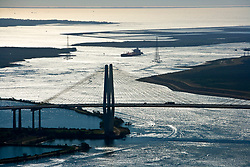 Scenic view of oil tanker underway approaching the Hartman Bridge in the Port of Houston at dusk from an aerial perspective.