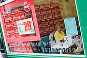 Seen through a takeaway and restaurant window of Coka-Cola (Coke) ads, two elderly ladies are about to pay their bill after their fish and chip supper in Bradford City Centre.