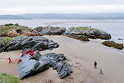 Children wearing red tops experience the outdoors on coastal rocks and other members of the public roam the beach that overlooks the estuary, on 7th October 2021, in Portmadoc, Gwynedd, Wales.