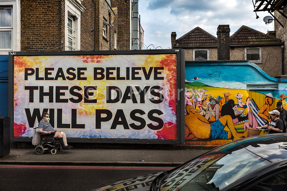 Masked figure passing billboard in Clapton, These Days Will Pass during the coronavirus pandemic on the 7th May 2020 in London, United Kingdom.
