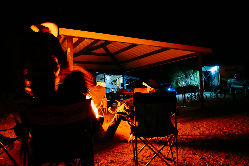 Gordon Booth, Heather Goodrich, and Josh Smith sit at the campfire with mountain bikes and RVs in the background.