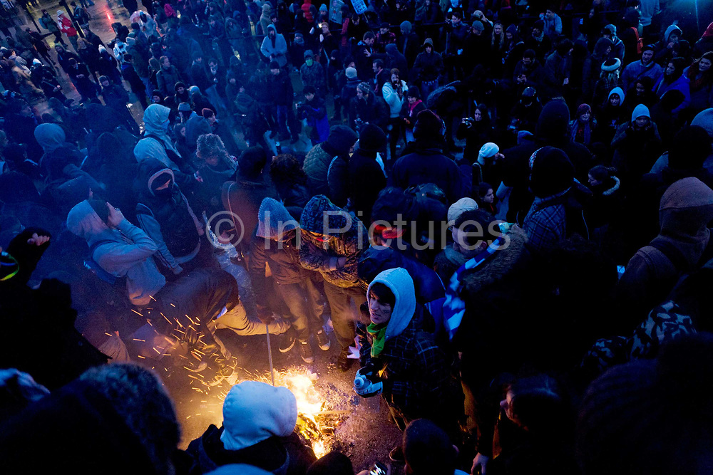 Young students and small fire during protest against government education cuts in Trafalgar Square. Holding a variety of splinter marches, students were campaigning against plans to raise tuition fees in England to up to £9,000 per year, with a vote expected in the House of Commons before Christmas. Police arrested 153 people during clashes in London on the third day of protests against plans to raise student tuition fees. The day ended with a stand-off with police in Trafalgar Square.
