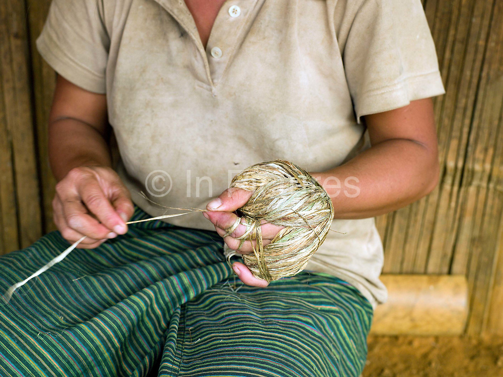 A Hmong woman twisting lengths of hemp bark together to form one long yarn, Ban Long Kuang, Houaphan province, Lao PDR. The yarn is wrapped around the hand in a figure of 8 creating a ball shape. Making hemp fabric is a long and laborious process; the end result is a strong durable cloth with qualities similar to linen which the Hmong women use to make their traditional clothing. In Lao PDR, hemp is now only cultivated in remote mountainous areas of the north.