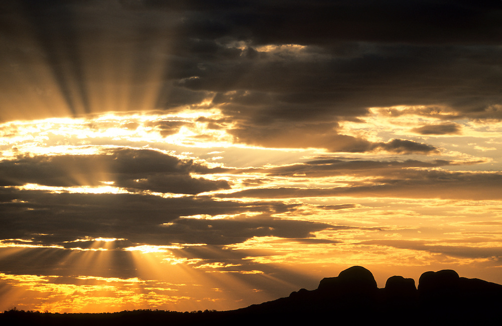 Australia, Uluru-Kata Tjuta National Park, Sun bursts through clouds behind Kata Tjuta (The Olgas), near Uluru (Ayer's Rock)