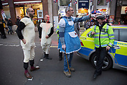 Group of friends on a Christmas day out in central London, UK. Dressed as Bo Peep and a flock of sheep, after the popular nursery rhyme. Here Bo Peep asks the police if they have seen his sheep, as he can't find them. The police join in for fun.