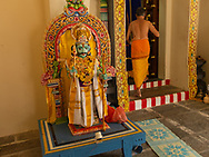 Hindu religious officiant and murti (deity or ceremonial statues). Sri Mariamman Temple. Chinatown. Singapore