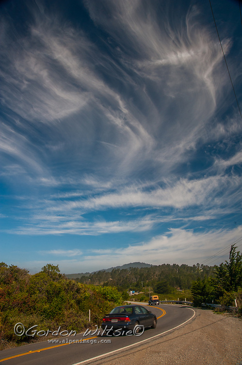 Cars drive along Skyline Boulevard below Cirrus clouds hovering above the California Coastal Mountains in the San Francisco Bay Area.