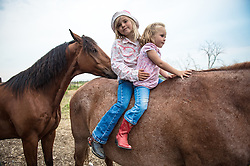 "The Nature Conservancy's Matador Ranch Operations Manager Charlie Messerly's daughters Layla, 5, and Janae play with their horses in Eastern Montana. The ranch is using innovative ways to leverage conservation gains, in which ranchers can graze their cattle at discounted rates on Conservancy land in exchange for improving conservation practices on their own ""home"" ranches. In 2002, the <br /> Conservancy began leasing parts of the ranch to neighboring ranchers who were suffering from  severe drought, offering the Matador's grass to neighboring ranches in exchange for their  participation in conservation efforts. The grassbank has helped keep ranchers from plowing up native grassland to farm it; helped remove obstacles to pronghorn antelope migration; improved habitat for the Greater Sage-Grouse and reduced the risk of Sage-Grouse colliding with fences; preserved prairie dog towns and prevented the spread of noxious weeds. (Photo By Ami Vitale)"