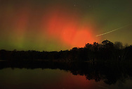 The Northern Lights shine in the sky over the lake at Fancher-Davidge Park in Middletown on Oct. 30, 2003 at about 7:30 p.m. The white line above the trees is the lights from an airplane during the 30- second exposure.