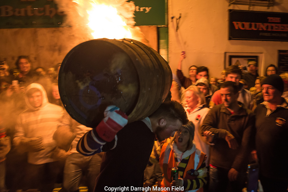 Locals scream support as a focused young man runs with a burning barrel on his back.