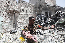 Jul 2, 2017 - Mosul, Iraq - An ISOF CTS sniper helps an infant and its family clear rubble near Al-Nuri Mosque days after the Iraqi government declared the Islamic State was defeated in Mosul. Heavy fighting continued as newly liberated residents flee in droves from the last ISIS held area in Mosul's Old City neighborhood. (Credit Image: ? Byron Smith via ZUMA Wire)