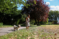 © Licensed to London News Pictures. 02/09/2019. London, UK. Carmen walking her dog on a sunny morning in a north London park covered with fallen autumn leaves. Photo credit: Dinendra Haria/LNP