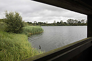 A view across the lake from one of the bird hides at Calvert Jubilee Nature Reserve on 27 July 2020 in Calvert, United Kingdom. On 22nd July, the Berks, Bucks and Oxon Wildlife Trust BBOWT reported that it had been informed of HS2's intention to take possession of part of Calvert Jubilee nature reserve, which is home to bittern, breeding tern and some of the UK's rarest butterflies, on 28th July to undertake unspecified clearance works in connection with the high-speed rail link.