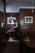 A male waiter lays a table at the Simpsons Tavern on the 24th September in East London in the United Kingdom. The Simpsons Tavern is a traditional chop house dating back to 1757. A chop house is a restaurant that specialises in steaks and chops.