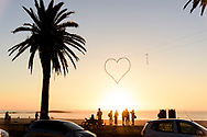 Beach goers walk along the Camp's Bay prominade at sunset outside Capetown, South Africa.  © Brett Wilhelm
