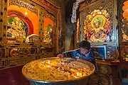 China, Tibet, at Druk Yerpa monastery. A young boy is lighting a huge butter lamp.