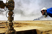 Aisa Bou Yabes, head of the Kuwait Oil Company firefighting team dispatched to southern Iraq inspects damage to oil well heads in Iraq's Rumaila field. The wells were set on fire with explosives by retreating Iraqi troops when the US and UK invasion began. Seven or eight wells were set ablaze. The Rumaila field is one of Iraq's biggest oil fields with five billion barrels in reserve. Many of the wells are 10,000 feet deep and produce huge volumes of oil and gas under tremendous pressure, which makes capping them very difficult and dangerous. Rumaila is also spelled Rumeilah.