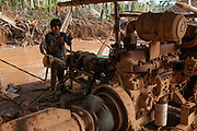 A miner controls an engine adapted to suck and eject mud from a flooded hole in the Peruvian Amazon, the mud contains gold that is separated by gravity as it slides down a ramp. Boca Colorado, Peru.