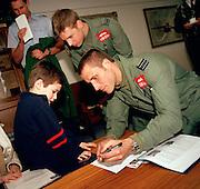 Pilots of the 'Red Arrows', Britain's Royal Air Force aerobatic team sign autographs for young visitor to RAF Scampton.