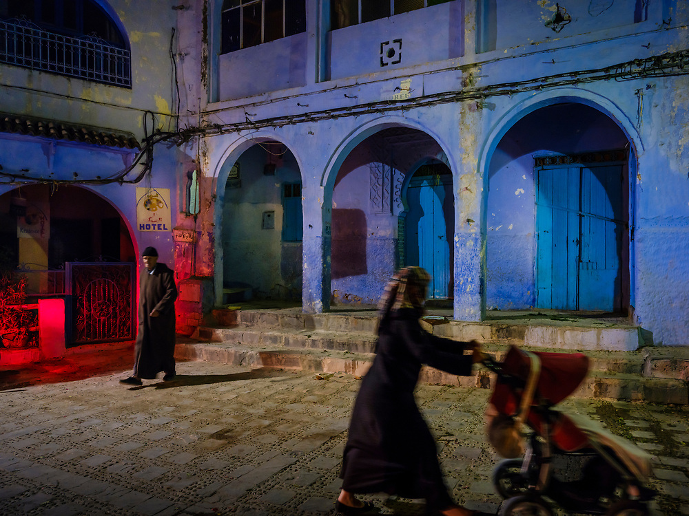 CHEFCHAOUEN, MOROCCO - CIRCA APRIL 2017: People walking by a square in Chefchaouen at night. This is a popular tourist destination in Morocco.