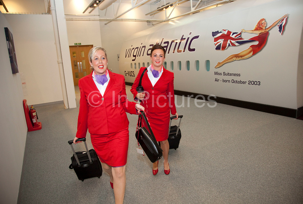 Just one week away from getting their 'wings' these flight attendants proudly wear their red uniforms. Virgin Atlantic air stewardess and steward training at The Base training facility in Crawley. Potential hostesses are put through a gruelling 6 week training program, during which they are tested to their limits. With exams every day requiring an 88% score to pass. The Base is a modern environment for a state of the art airline training situated next to Virgin Atlantic's HQ.