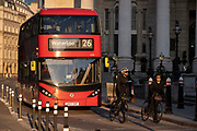 With the columns of Royal Exchange in the background, cyclists and a London bus are queued at a red light in at Bank Triangle and  in the City of London, the capital's financial district, on 27th February 2021, in London, England.