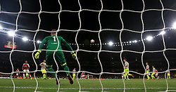 Arsenal's Alexis Sanchez (right, obscured) scores his side's second goal of the game during the Europa League match at the Emirates Stadium, London.