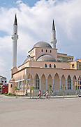 Street scene with a mosque and two women on bicycle. Shkodra. Albania, Balkan, Europe.